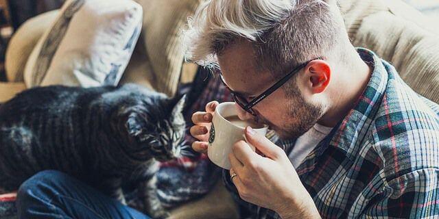 Jóven bebiendo una taza de café junto a su gato.