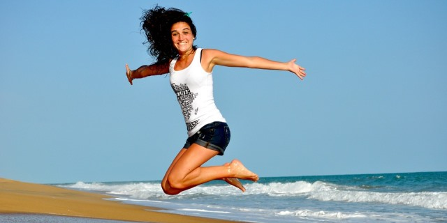 Chica saltando en la playa.
