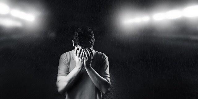 Hombre con las manos en la cara, representando la depresión postvacacional.