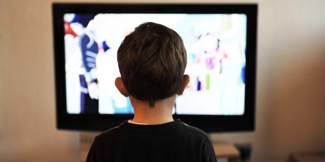 Niño de espaldas viendo la televisión.
