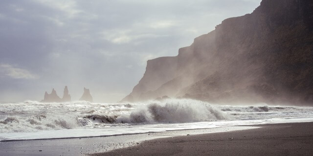 Ola rompiendo en una playa cercana a un sistema montañoso.
