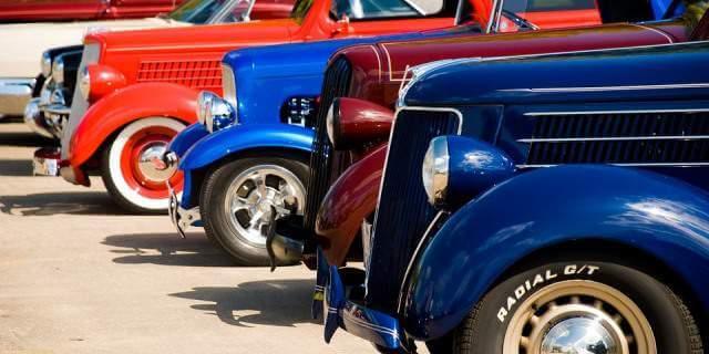Varios coches clásicos expuestos en un evento de fin de semana.
