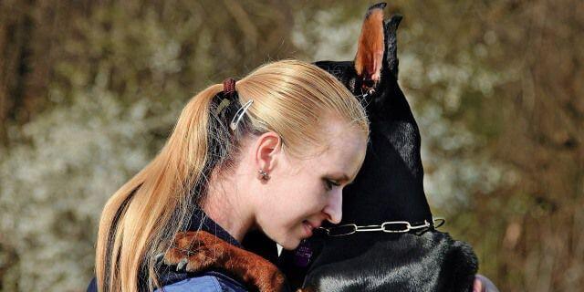 Chica abraza con cariño a un dóberman.