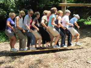 Team members stand single file with one foot on each board, walking as one unit.