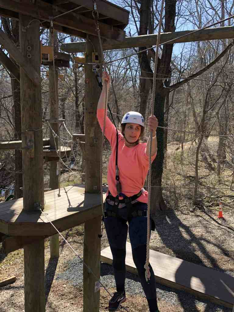 A woman swinging like Tarzan between ropes on a challenge course.