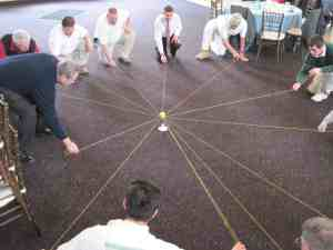 A group of men in business clothes try to suspend a ball on a ring, supported by outstretched pieces of string.