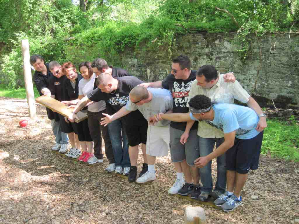 A group stands in a line and passes a 2x4 board down the line.
