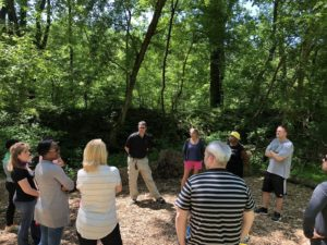 A group of people standing in a circle outdoors, surrounded by trees, facing the group facilitator.