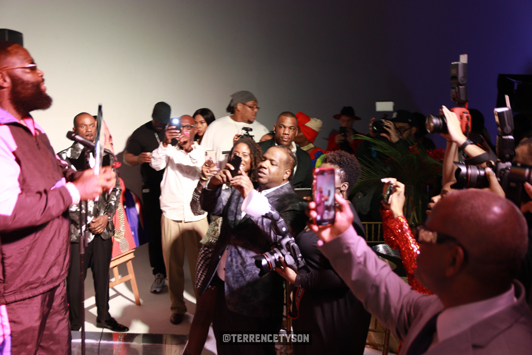 Rick Ross on stage with award in his hand with people taking pictures of him