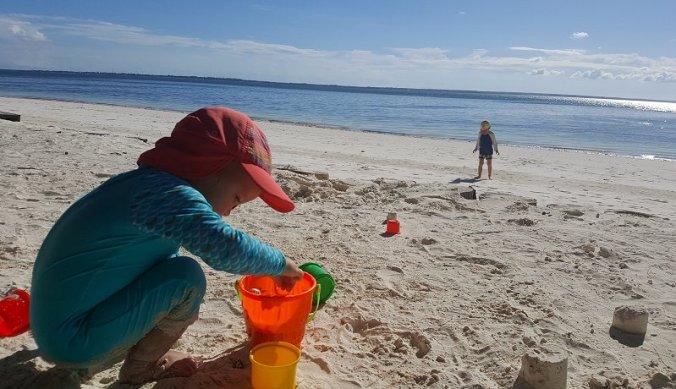 Spelen op het strand van Zanzibar met schepje en emmertje