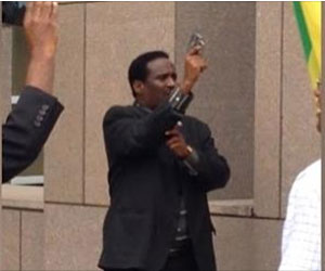 A TPLF security thug at the Ethiopian Embassy brandishing and firing live bullets towards peaceful protesters