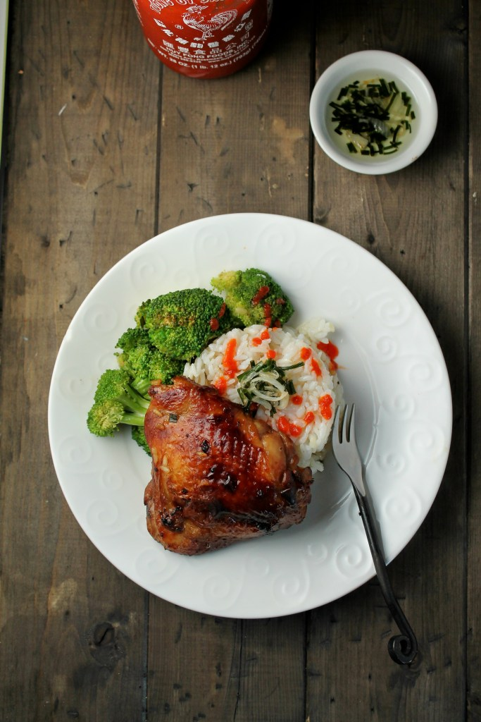 white plate of a golden gone in chicken thigh atop a mound of white rice with scallion oil, sriracha, steamed broccoli from overhead on a dark wooden table