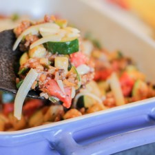 a blue ceramic baking pan with handles filed with brown rice, zucchini, tomotes, basil, and cheese and a serving spoon of coconut wood scooping up a serving