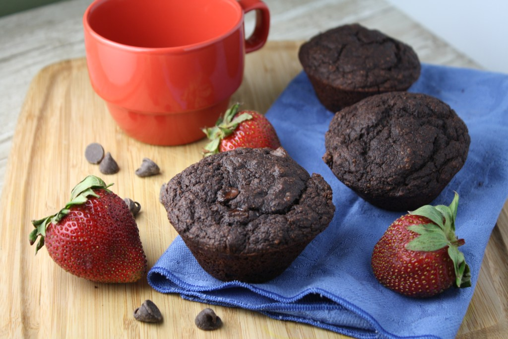 3 dark chocolate muffins on a wooden cutting board surrounded by fresh whole strawberries
