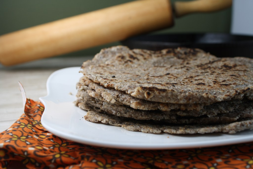 close up eye level stack of 4 gluten free tortillas with cook marks and a wooden rolling pin in background