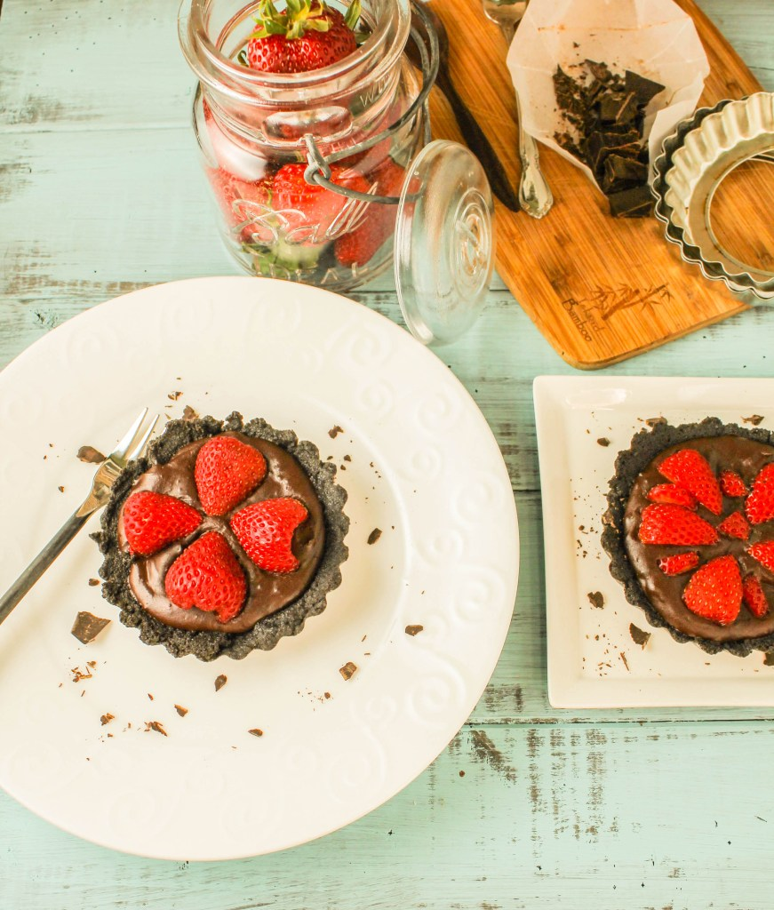 over head shot of 4 halved strawberries atop a thick chocolate ganache in a chocolate cookie crust on a white plate and a turquoise blue background