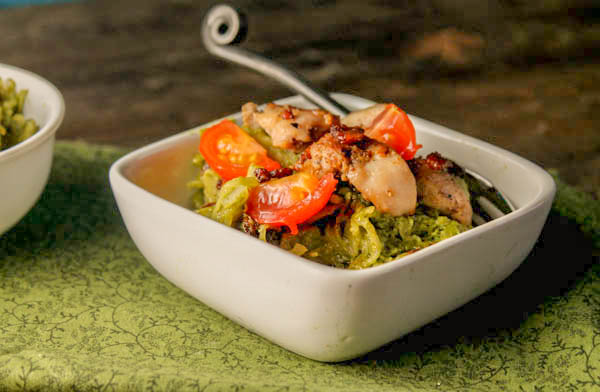 eye level shot of pesto spaghetti squash noodles in a white bowl topped with browned chicken thighs, crispy bacon. and chopped tomatoes