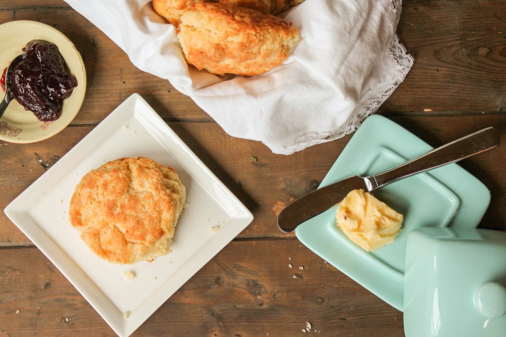 a fluffy biscuit on a white plate from overhead on a dark wooden surface with a turquoise butter dish