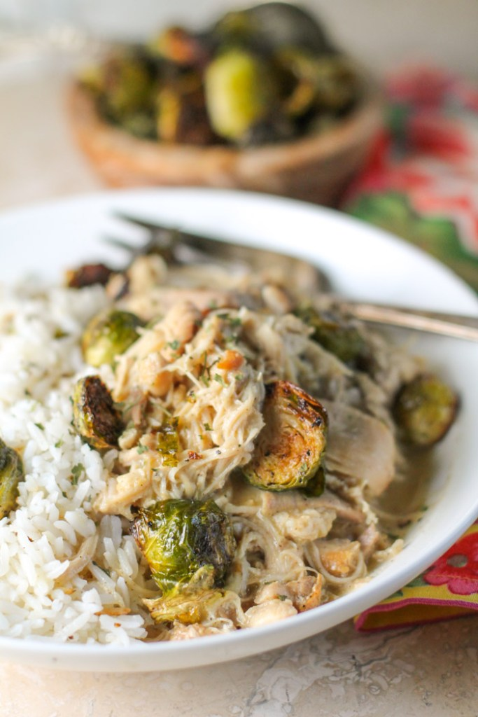 vertical image of a plate on tender shredded chicken and roasted brussel sprouts in a white bowl with a tarnished silver fork