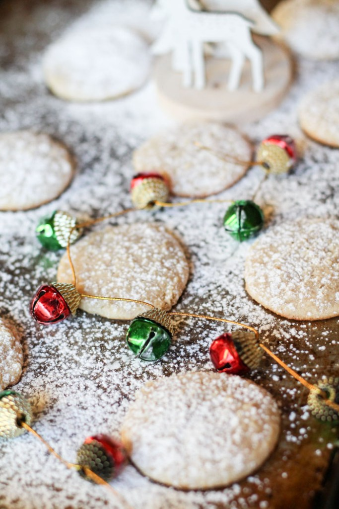 vertical image of powdered sugar dusted cheescake cookies on a cookie sheet with a garland of red and green ornaments winding around