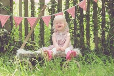 Tessa Trommer Fotografie Erfurt Kinderfotografie Kinderlachen Gummistiefel Garten Bollerwagen Wimpelkette Rosa