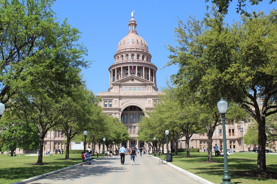 View of the Texas Capitol building with people walking on the sidewalk in front.