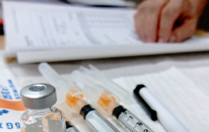 In the foreground are immunization plungers and vials. In the background is a hand resting on paper.