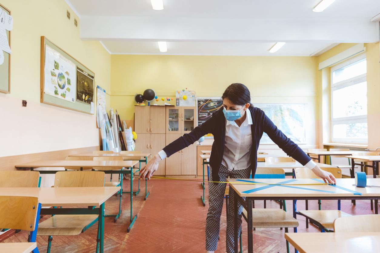 Teacher in a classroom, measuring distance between desks. The teacher is wearing a face mask.
