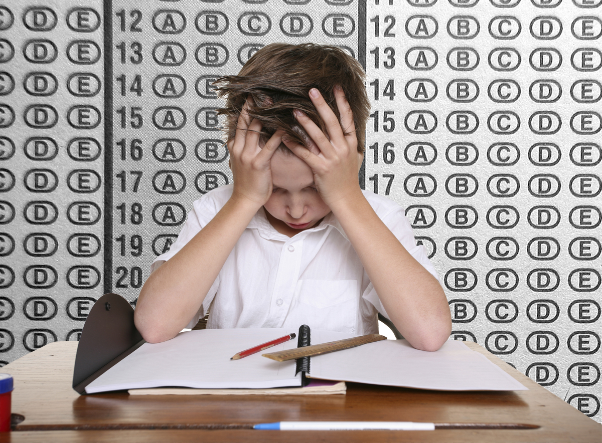 Student with head in their hands, staring at a desk covered in materials. Behind them is the answer grid of a standardized test.