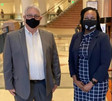 Candis Houston of Aldine A-F-T stands next to a union member from HOPE in the Capitol. Both wear masks.