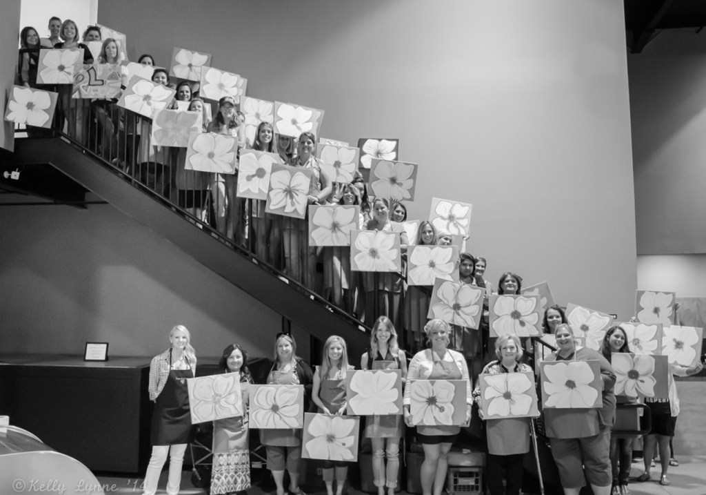 large group of women at a paint party holding finished pieces