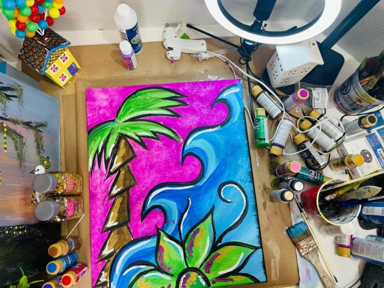 acrylic painting with palm tree, flower and waves with supplies used to paint