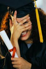 Smiling Graduate Covering Face