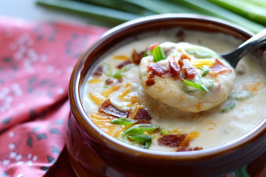 Spoon full of baked potato soup recipe topped with bacon and cheese