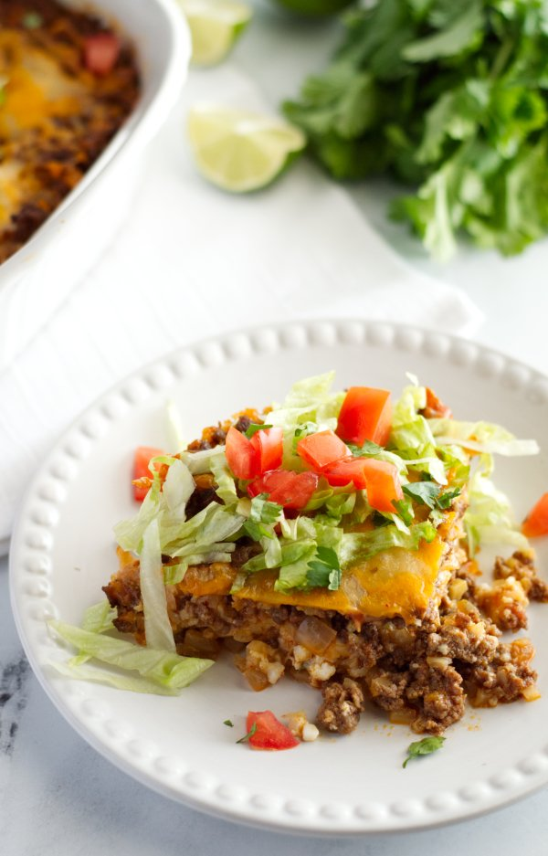 Taco casserole on a plate with lettuce and tomato