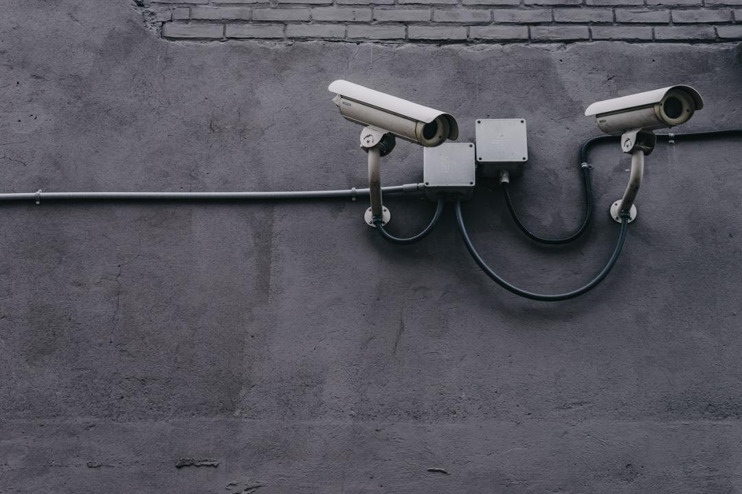 a pair of cctv cameras on the side of a building