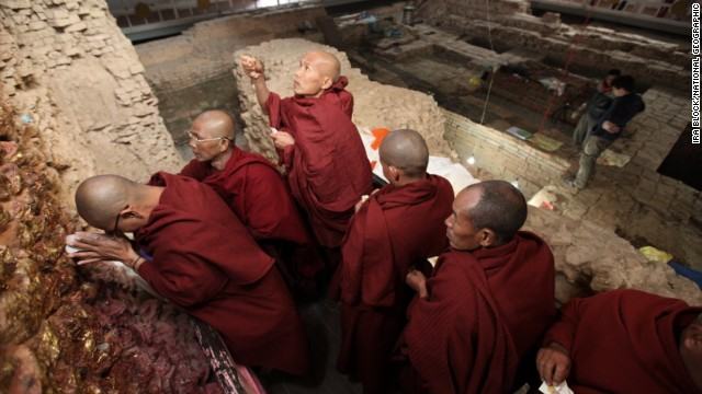 Pilgrims meditate at the Maya Devi Temple, with ancient remains in the background/Source: CNN.com