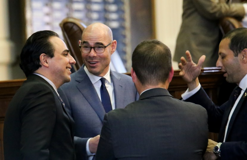 Texas House Speaker Dennis Bonnen (center) speaks with state Representatives Terry Canales (left) and Poncho Nevárez (right).