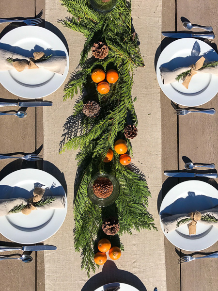 For the table, I kept it very simple and used white plates with linen napkins, a linen runner, some cedar branches, mandarines from our garden, and pine cones.