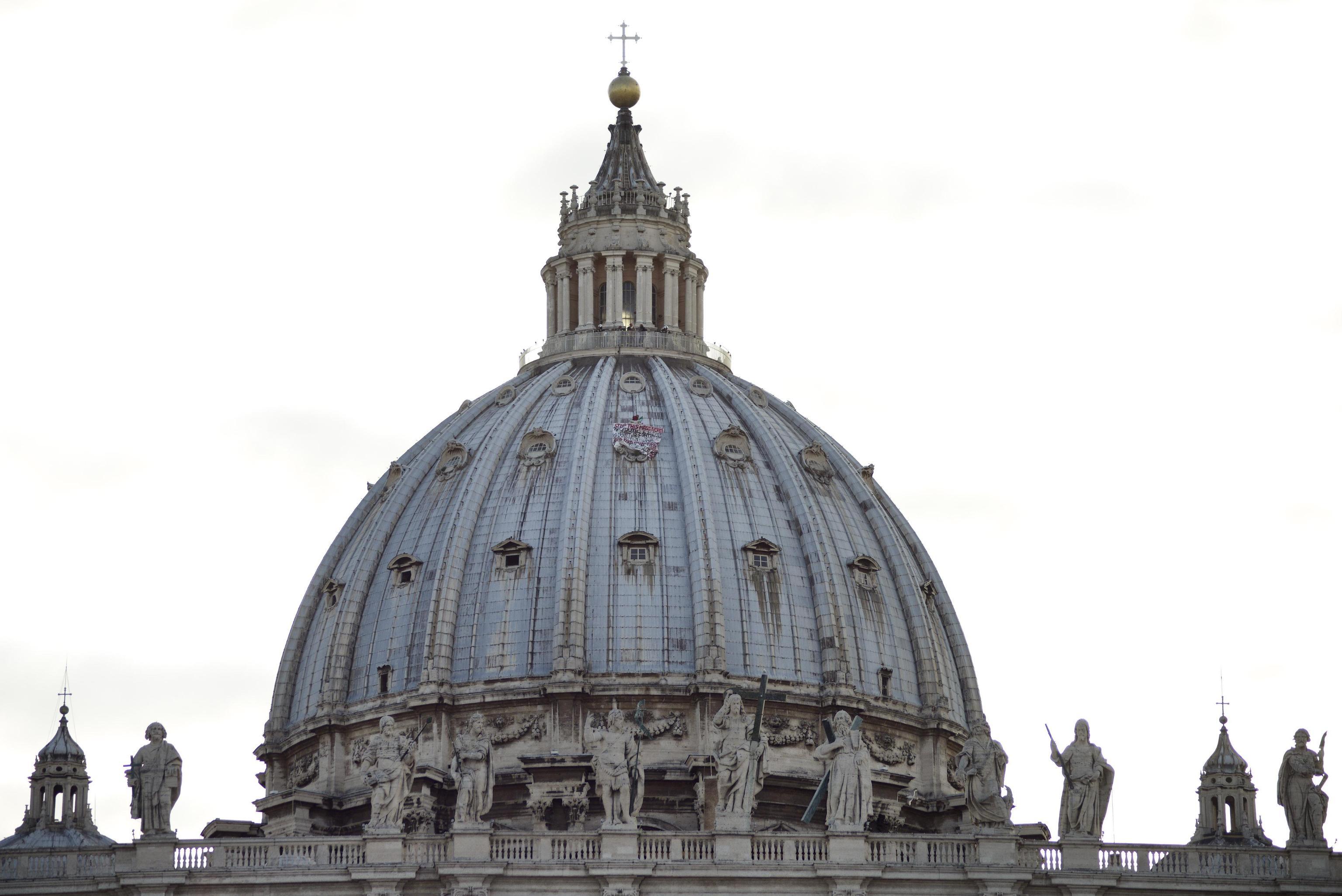Roma uomo su cupola San Pietro con striscione e bandiera