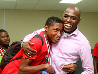 Olympic gold medalist Michael Sealey is greeted by Secretary of the Division of Education, Youth Affairs, and Sport (DEYAS) Huey Cadette at the ANR Robinson International Airport on Wednesday (March 25, 2015).