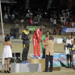 Andwuelle Wright, centre, stands atop the podium after his gold medal-winning endeavour in the Boys under-20 long jump.