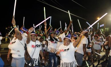 Wearing white shirts, masqueraders from the band Bago Limers light up the streets on Monday with glow sticks.