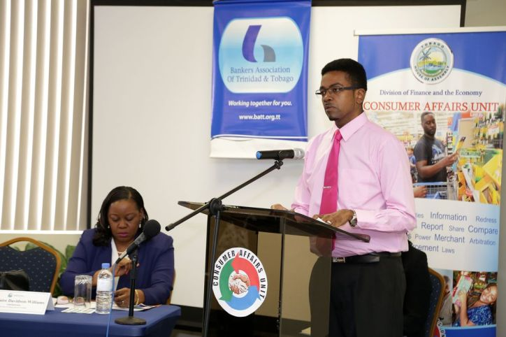Consumer Affairs Unit Manager Langdon Phillips, right, speaks at the function. Also in photo is Administrator of the Division of Finance and the Economy Claire Davidson-Williams.