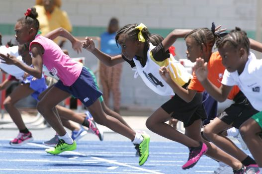 The Girls Under 9 100M competitors power off the start line.