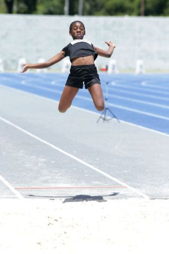 Janae De Gannes of St Anthony's Primary goes airborne in the girls under 13 long jump event, which she eventually won.