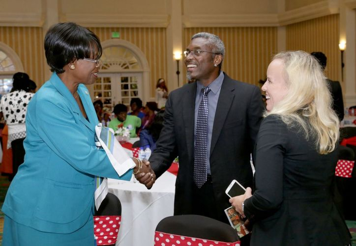THA Secretary of Health, Wellness and Family Development Dr Agatha Carrington, left, greets president and founder of the Down Syndrome Family Network Glen Niles as she is introduced by volunteer coordinator Laura Cotton at the opening of the World Down Syndrome Day Conference.