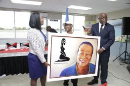 A portrait of Calypso Rose is held by Secretary for Tourism, Culture and Transportation Nadine Stewart-Phillips, THA Chief Secretary Kelvin Charles, and Calypso Rose.