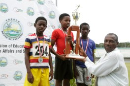 Co-ordinator of the Multi-cultural Education Unit of the Division of Education Rennison Quashie, presents 3K road race winner Nyah Davis of Mt St George Methodist Primary School with the trophy while second placed Ben Israel Bannister of Mason Hall Government, left, and Yeshua Prescod of Pentecostal Light and Life Ministries School look on.