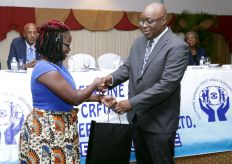 TWCU liaison officer Melissa George presents THA Chief Secretary Kelvin Charles with a token of appreciation.